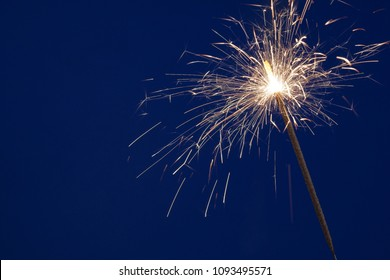 Burning christmas sparkler on blue background with copyspace