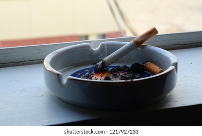 A Burning Cigarette and Ashtray on a Window Sill