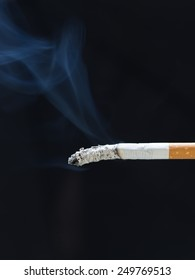 burning cigarette with smoke  isolated on black