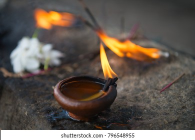 Burning clay oil lamp with white flowers a buddhist and hindu temple as a traditional offerings in Sri Lanka