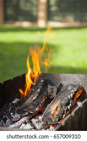 Burning coals in the grill. Charcoal barbecue blazing and growing in tray. BBQ