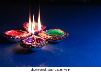 burning decorated ceramic oil lamp diya, on Happy Diwali, Shubh Diwali meaning with beautiful dark blue background, copy space