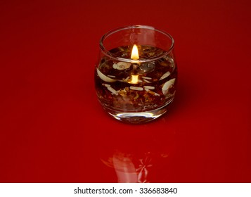 Burning decorative candle in a glass jar, filled with bits of shells and very small pebbles, isolated on a red background with a subtle reflection. Horizontal view.