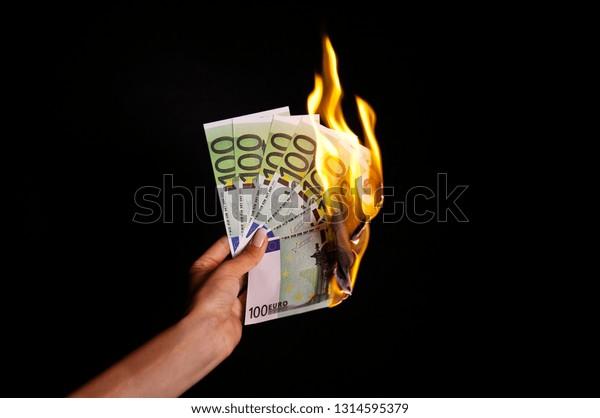 Brennen von Euro-Banknoten in Händen einzeln auf schwarzem Hintergrund. 100 Euro-Banknoten