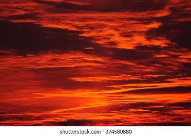 Burning evening sky at sunset. The sun is leaving the last sunbeams behind which color the heaven in dynamic illumination.