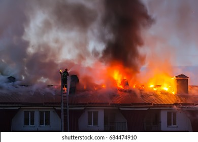 Burning fire flame with smoke on the apartment house roof in the city, firefighter or fireman on the ladder extinguishes fire.