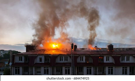 Burning fire flame with smoke on the apartment house roof in the city, firefighter on the ladder extinguishes fire.