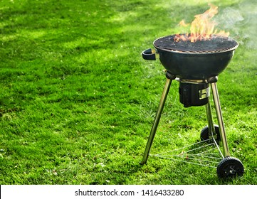 Burning fire with flames in a portable BBQ outdoors on a green spring lawn with copy space