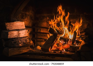 Burning fire in open fireplace with wooden fuel (firewood). SELECTIVE FOCUS