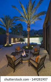 Burning fire pit surrounded by empty chairs on terrace of California home