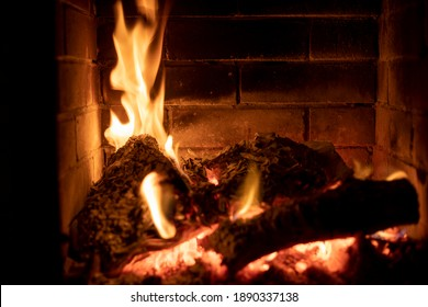 burning fire in a stone fireplace with wood with an open door, cozy home