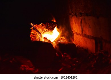 A burning fireplace in a country house. A soft fire for a cozy evening. Warm light