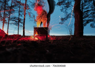 Burning firewood in the barbecue against the abstract person silhouette.