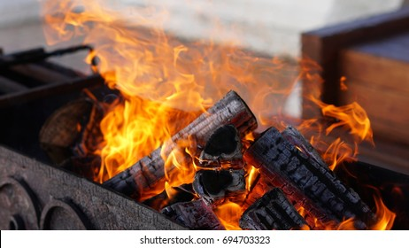 Burning firewood in a barbecue grill to get charcoal