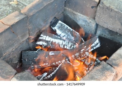 Burning firewood with black cracked surface covered with white ashes. Terracotta charred red bricks in old charcoal mangal. Smoldering wood logs texture with blurred flames. Fiery background.