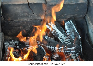 Burning firewood with black cracked surface covered with white ashes. Smoky bricks in old mangal brazier. Charred wood logs texture with bright orange flames. Fiery background of barbecue.