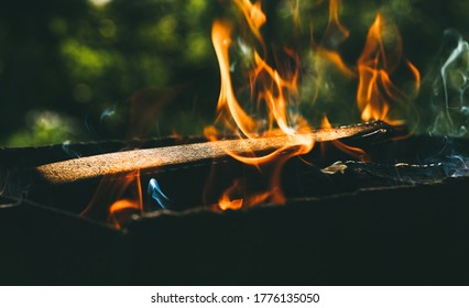 Burning firewood in a homemade barbecue on background of green foliage in garden. Firewood, fire and smoke close-up