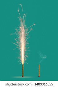 Burning firework with bright sparkes and smoke from burnt candle on a turquoise background, copy space. Concept of festive event.
