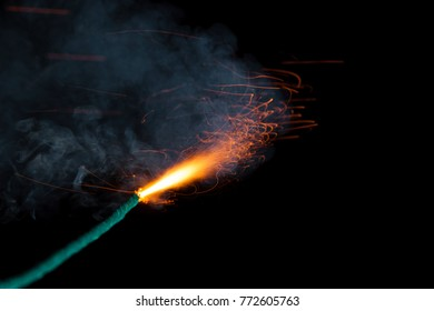 Burning fuse with sparks and grey smoke on black background