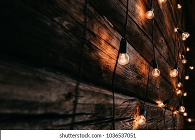 Burning garland on a wooden background. Evening wooden stage in the garden with lamps for parties.