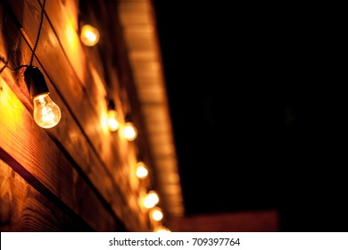 Burning garlands garland on a wooden background. Light bulbs on wooden background. Evening Wooden Stage In The Garden With Lamps For Parties Or Wedding