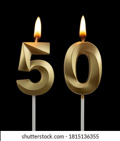 Burning golden birthday candles isolated on black background, number 50