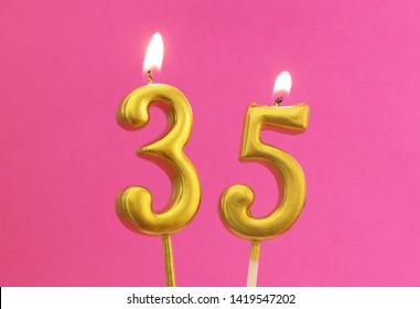 Burning golden birthday candles on pink background, number 35