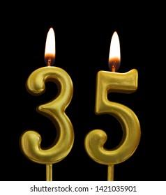 Burning golden birthday candles on black background, number 35
