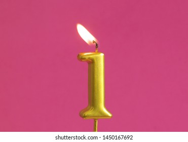 Burning golden birthday candles on pink background, number 1