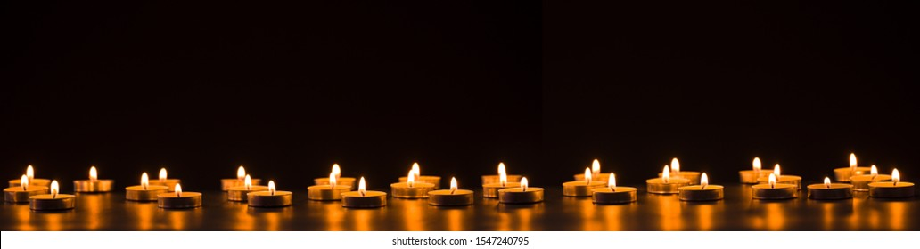 Burning golden candles on black background. Mourning, grief, mourning or Christmas concept.