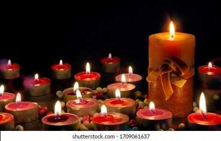 Burning golden candles on black background. grief, mourning or Christmas concept