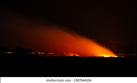Burning the grass on the roadside late at night
