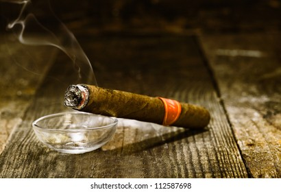 Burning handmade luxury Cuban cigar resting on an ashtray on an old wooden countertop in a nightclub or bar with copyspace