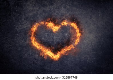 Burning heart - heart-shaped ring of fire and orange flames over a textured dark background with copyspace conceptual of love, romance and Valentines Day