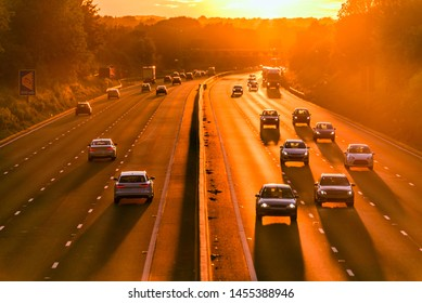 burning hot sunset on uk motorway with long shadows of moving car traffic in england