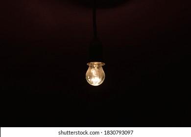 A burning incandescent lamp in a dark basement