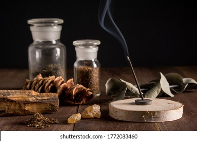 Burning incense and material of incense on wood background.