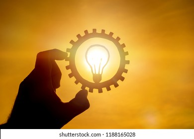 Burning lamp idea in a gear on a background of the sun, holding a businessman's hand. Business concept, innovation, thinking, creative, work.