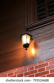 The burning lamp on a wooden wall of the building. The Dark background with the burning lamp vertically.