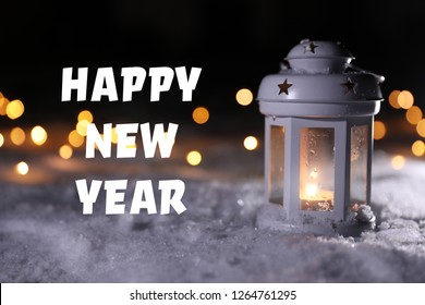 Burning lantern on snow and message HAPPY NEW YEAR against blurred background. Winter holidays