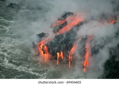 A burning lava flow is seen pouring over rock and into the ocean. Steam can be seen rising from the cold water as the molten lava enters it.