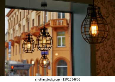 burning light bulbs of geometric shape against the background of a window through which a view of the buildings