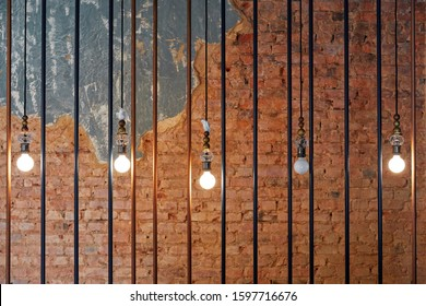 burning light bulbs, hanging in a row, behind iron bars, against the background of a brick wall