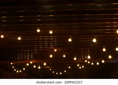 burning light bulbs on a wooden wall background