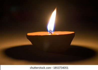 A Burning or LIT Diya (Clay Lamp) standing alone in the dark.