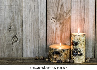 Burning log candles by acorns and old distressed rustic wooden background; wood holiday background with copy space
