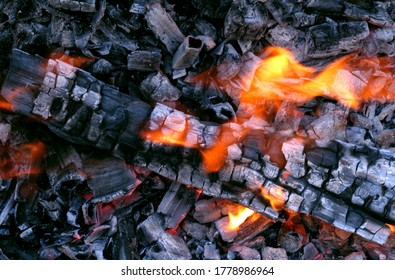 Burning log of wood close-up as abstract background. The hot embers of burning wood log fire. Firewood burning on grill. Texture fire. Smoldering fire. Smoking wood halloween banner background.
