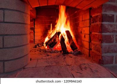 Burning logs flaming in fireplace.