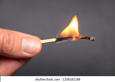 Burning match in female hand, isolated on black