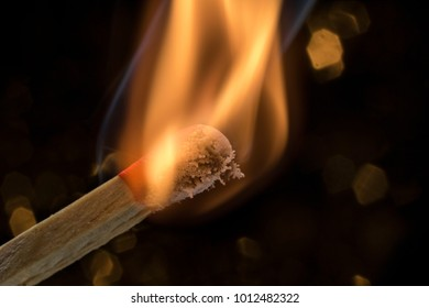 burning match in front of black background